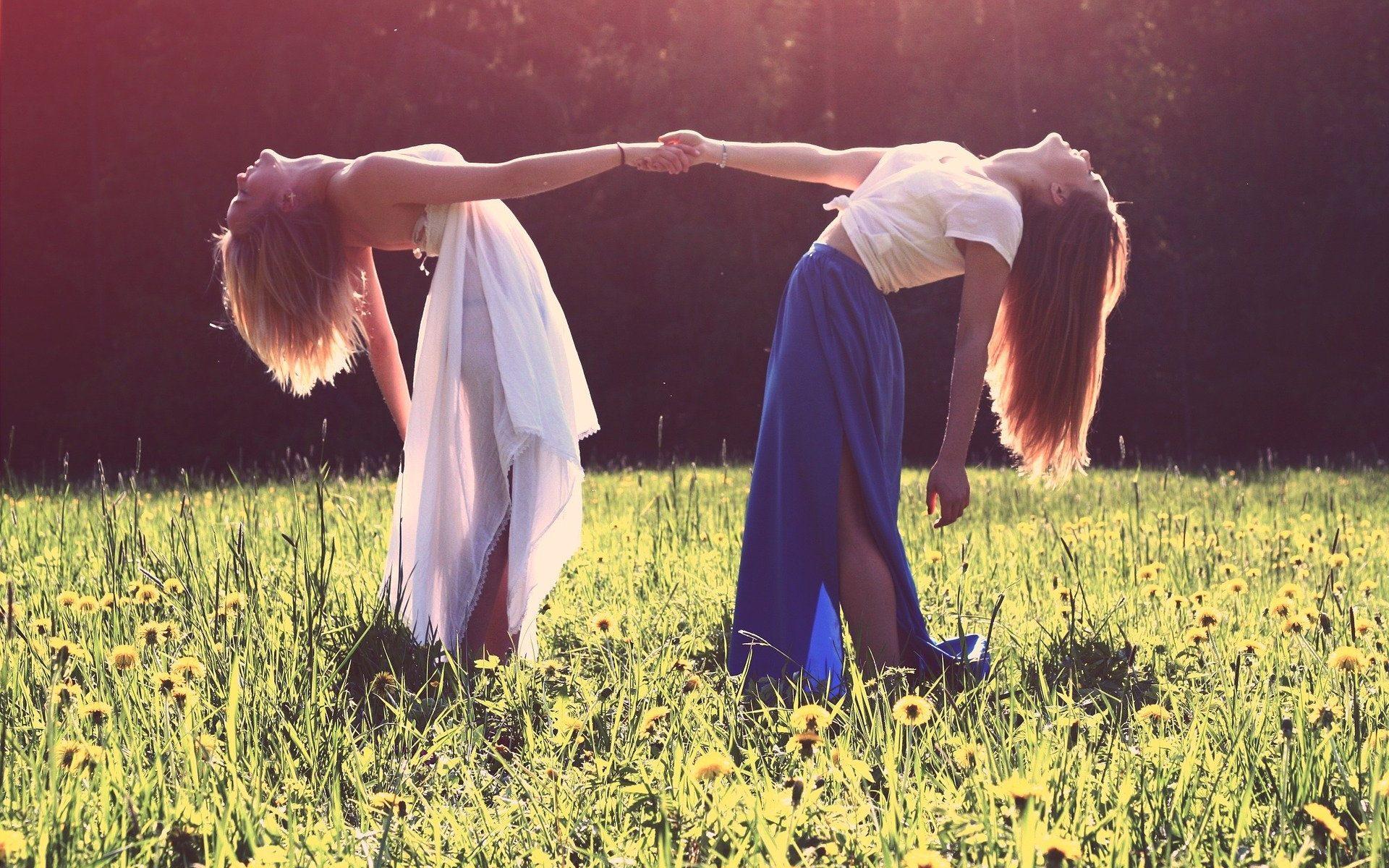 Zwei junge Frauen halten sich an einer Hand und drehen sich dabei auf einer Frühlingswiese im Kreis, ihre Oberkörper und Köpfe sind nach unten Richtung Blumenwiese geneigt. Lustvolle Sexualität liebt das Spiel und den Spaß!
