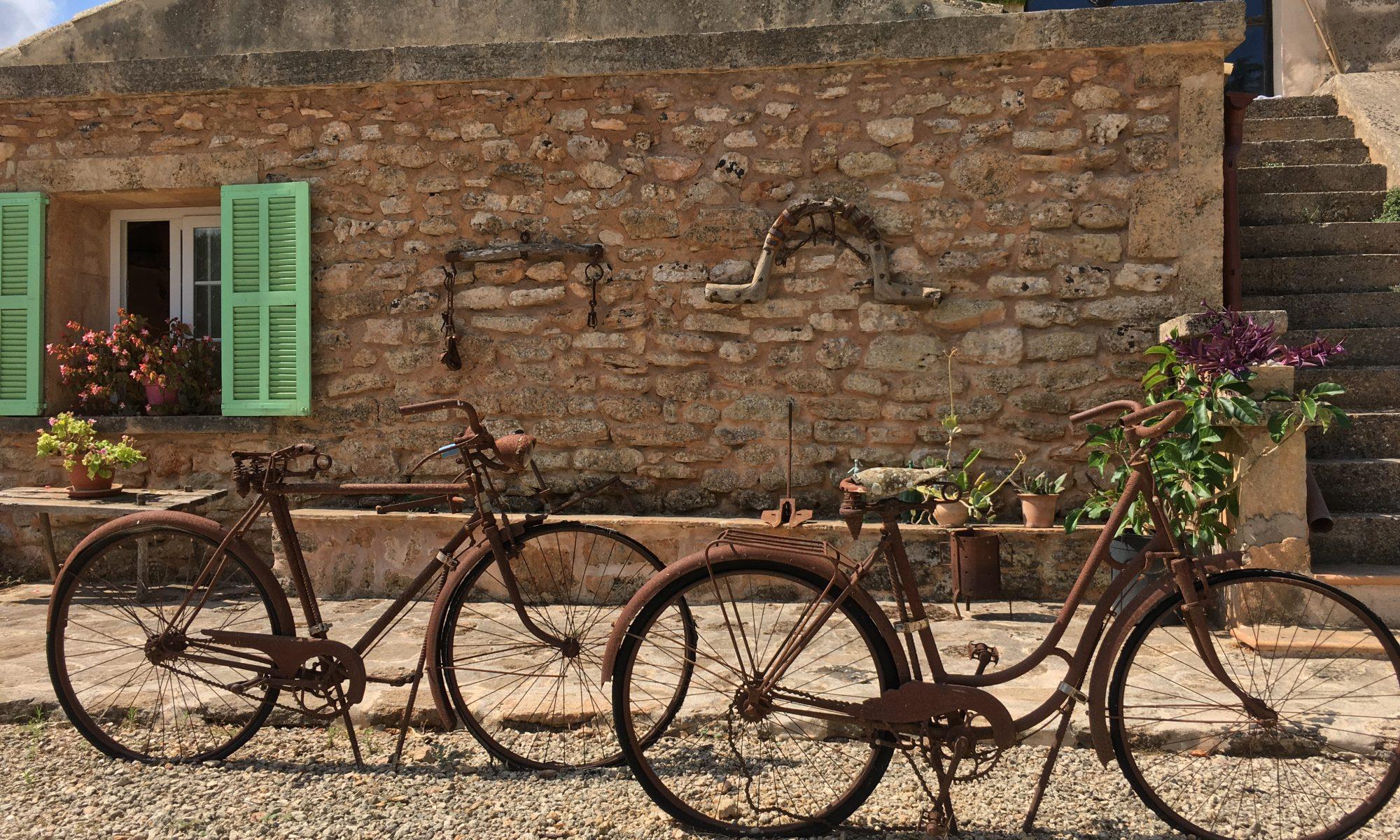 zwei Fahrräder vor einer sonnenbeschienenen Hauswand warten auf ihre Mitfahrerinnen, um gemeinsam neue Wege zu erkunden. Dabei unterstütze ich Sie gern mit systemischer Sexualtherapie und Paartherapie jetzt auf Mallorca